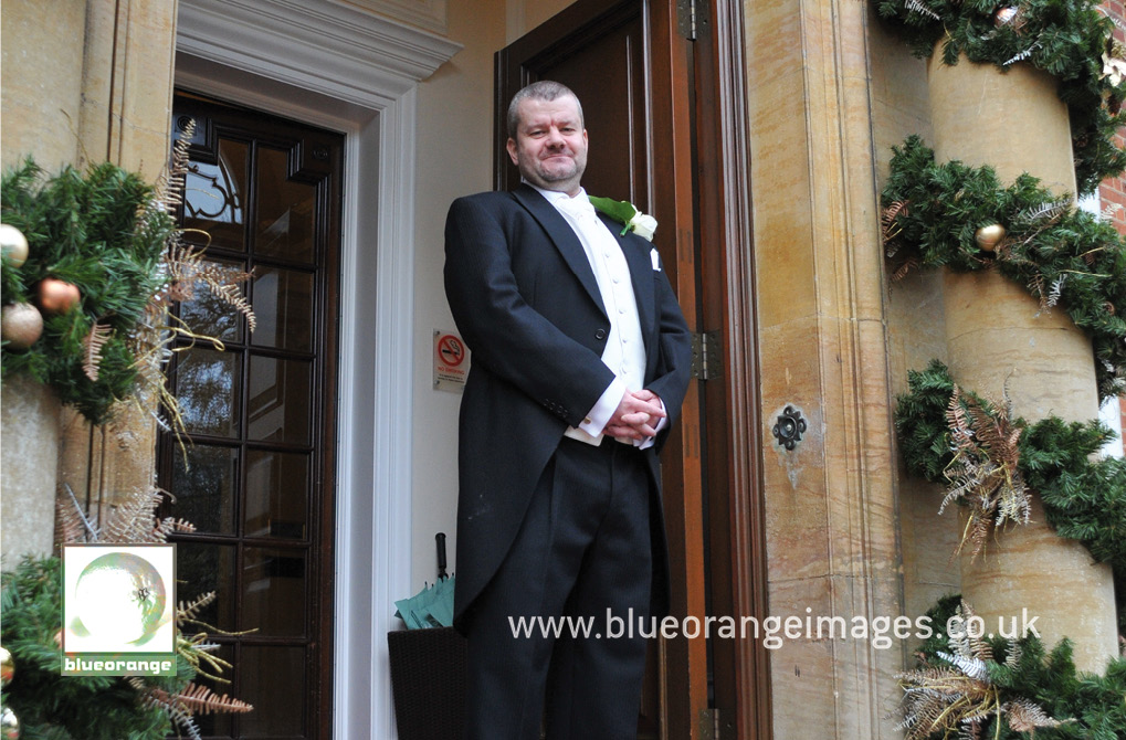 The bridegroom at the main entrance to Hunton Park wedding venue, Herts