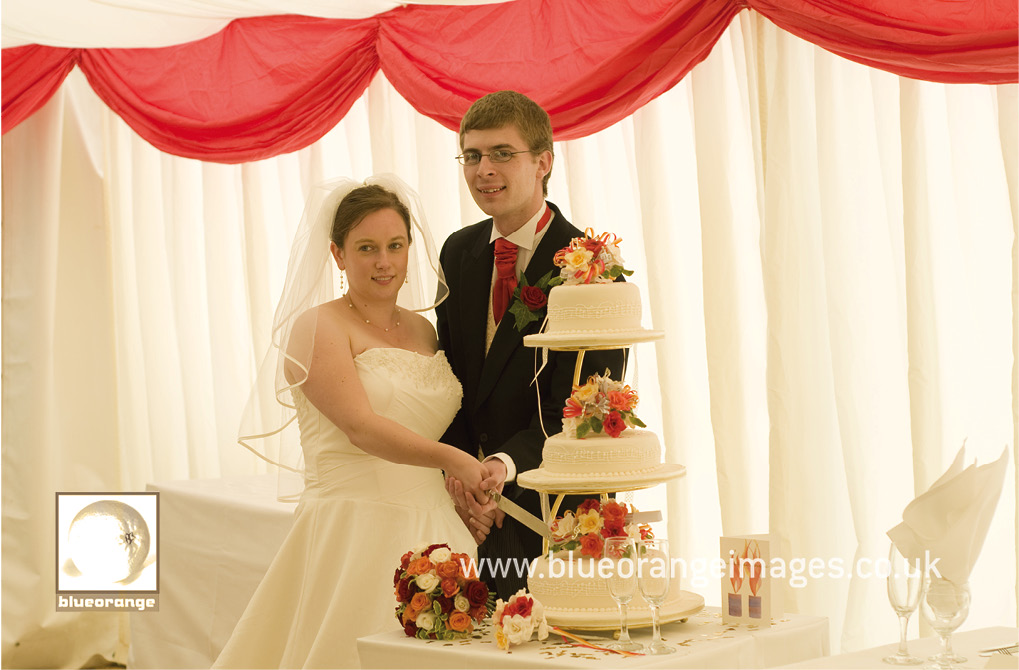 Hannah and John, the bride and groom, cutting the wedding cake