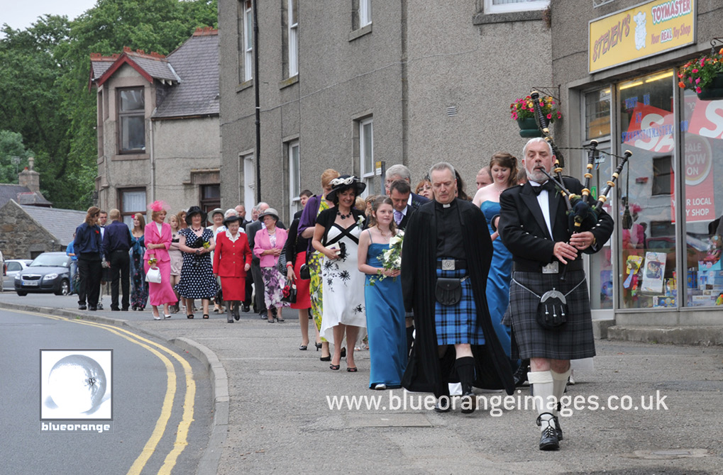 The wedding party parade down the street to the riverside, with the piper at the head of the procession
