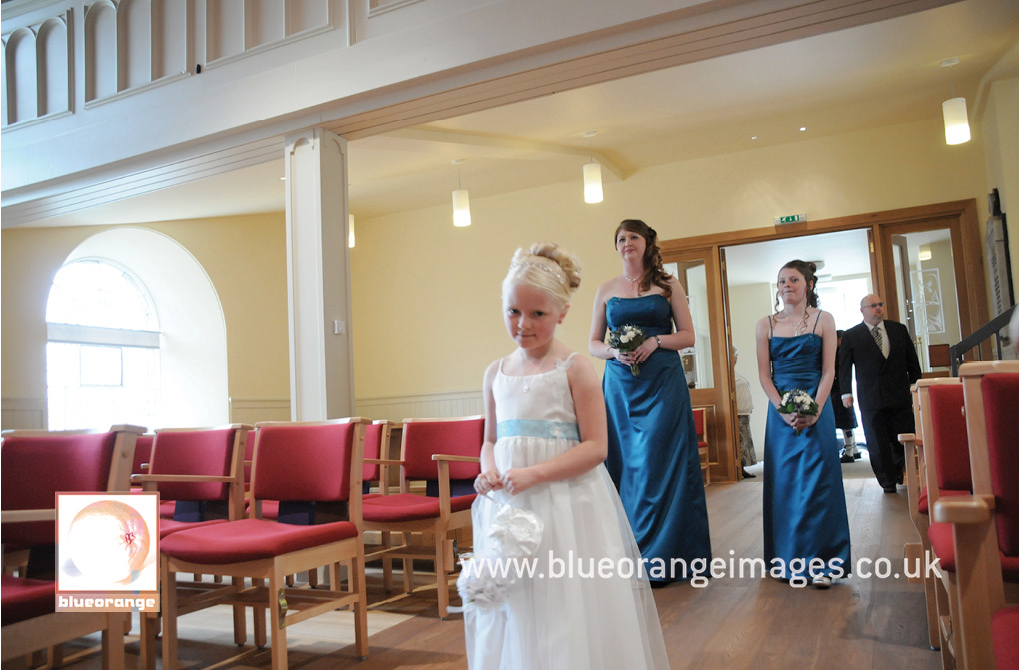 The bride, bridesmaids and flowergirl, walking down the aisle