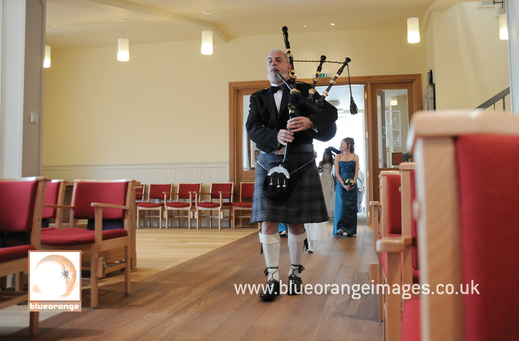 Bridal procession led into the church by kilted piper